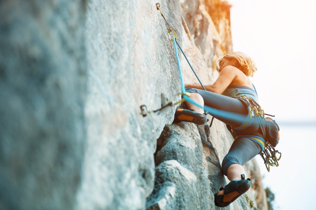 female rock climber on wall shot from below