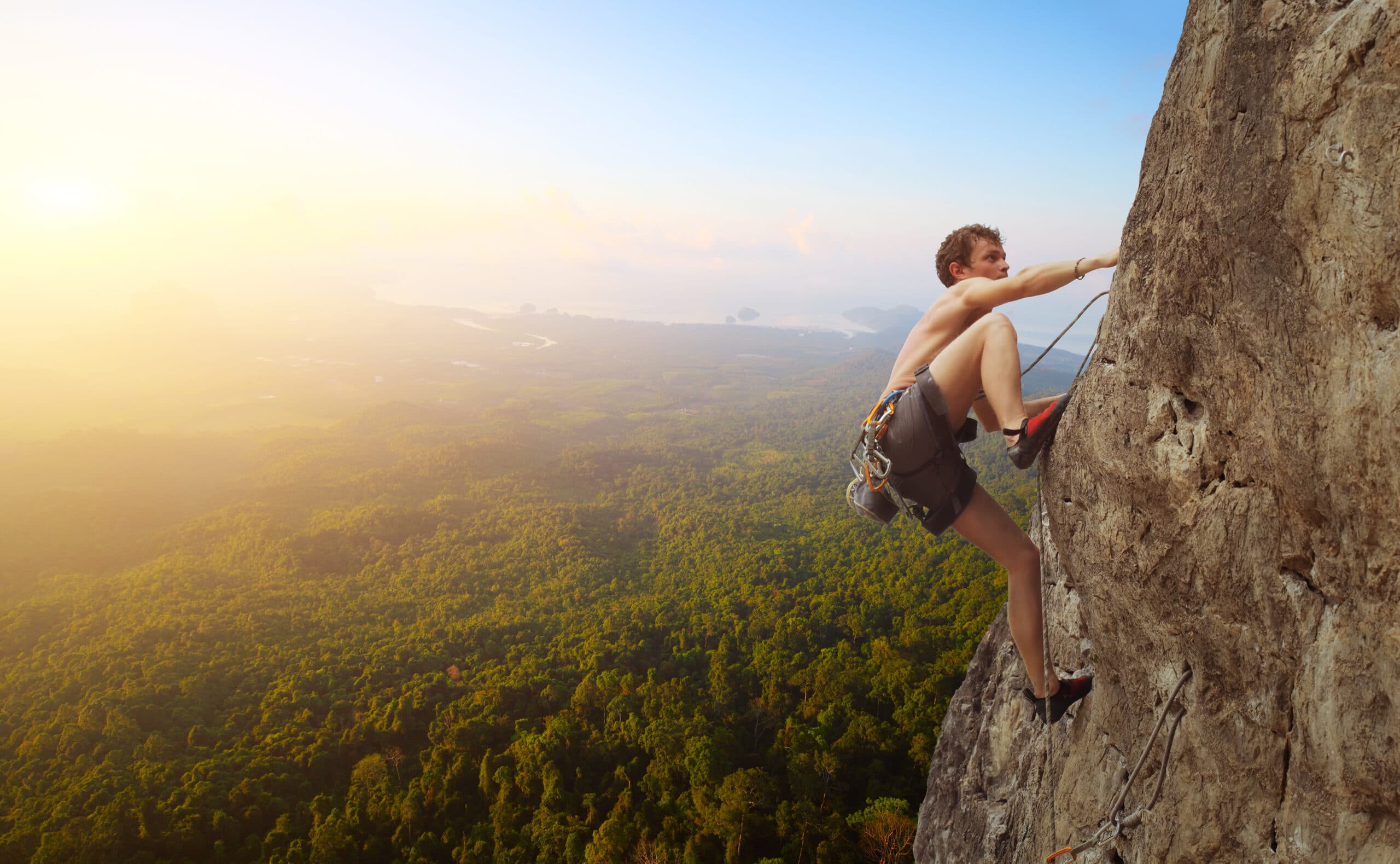 Young man climbs on a rocky wall in a valley with mountains at sunrise