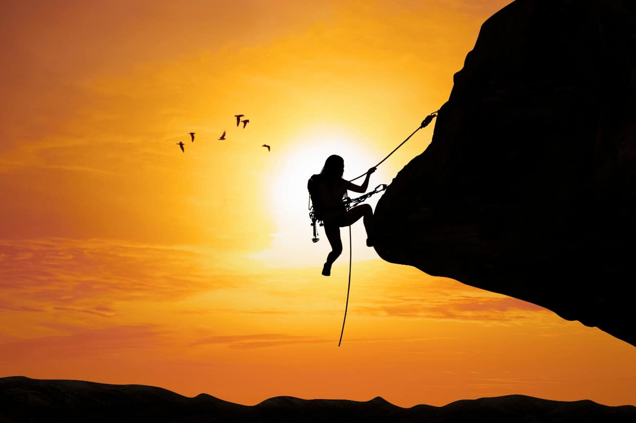 Woman silhouette rock climbing in front of sunrise