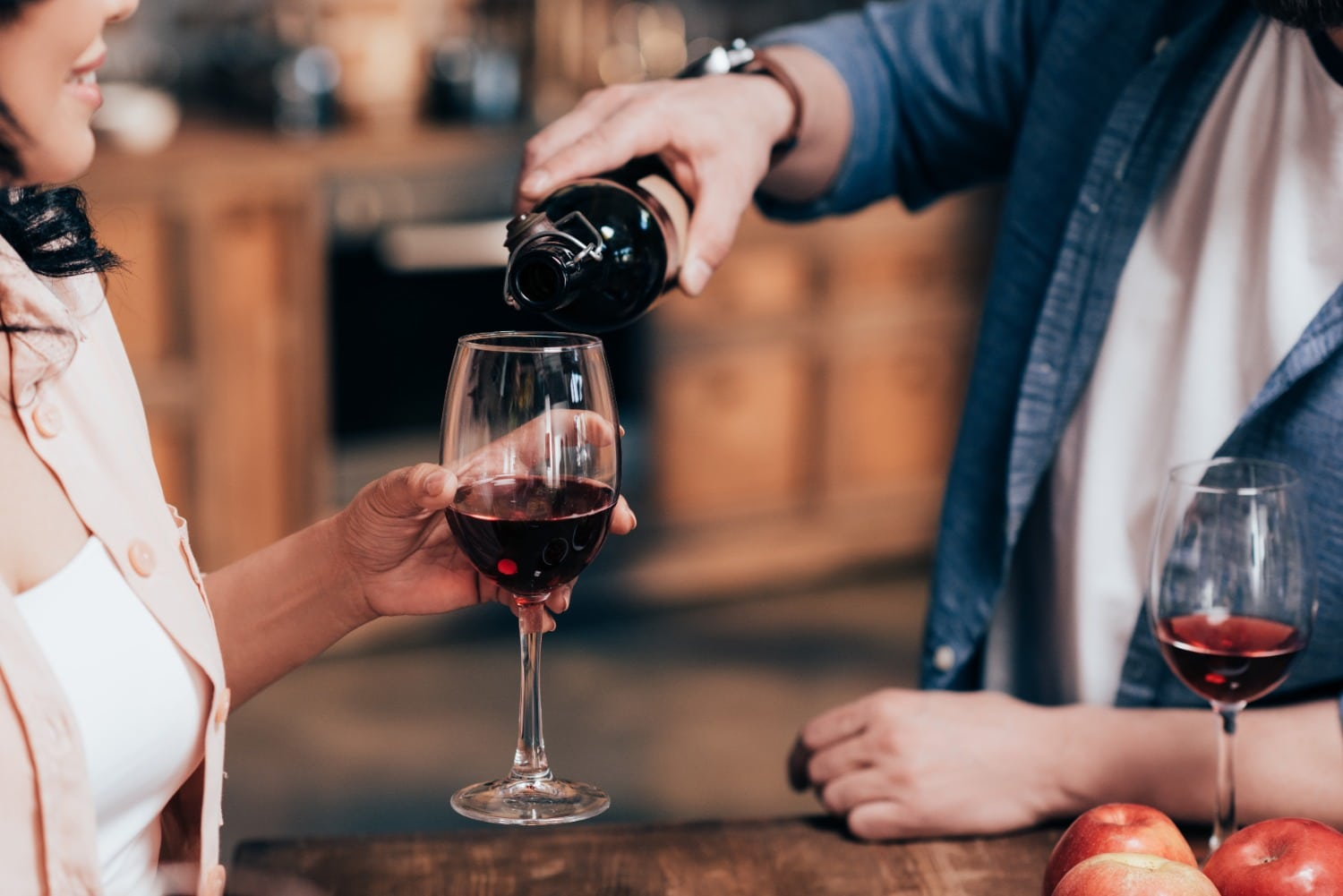 man pouring red wine for woman
