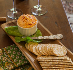 Pimento cheese and crackers rest on a wooden tray with two wine glasses in the background.
