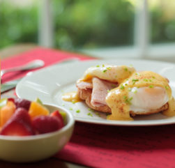 An Eggs Benedict with fresh fruit and orange juice.