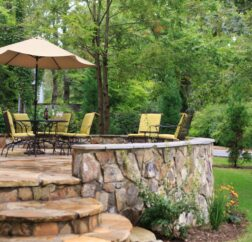 Chairs rest on the stone covered Chanticleer Inn with lush forests in the background and colorful flowers in the flower bed.