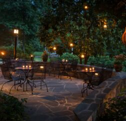 The back patio of the Chanticleer Inn shows candlelit tables in a dense garden at dusk.