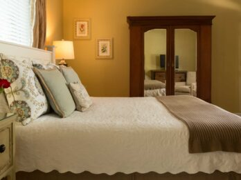 A room at the Chanticleer Inn shows a large bed with white linens, modern throw pillows, an antique side table with fresh roses, and a mirrored dresser.