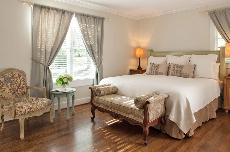 view of king-size bed next to large window in Room 11